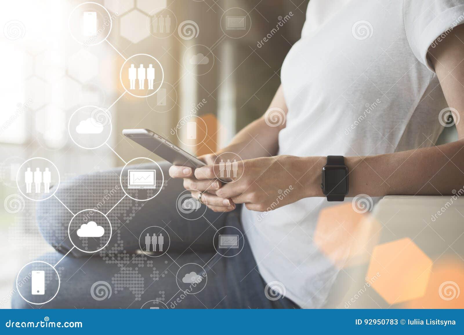 Närbild av smartphonen i händer av den unga hipsterkvinnan I förgrund är faktiska symboler med moln, folk, grejer