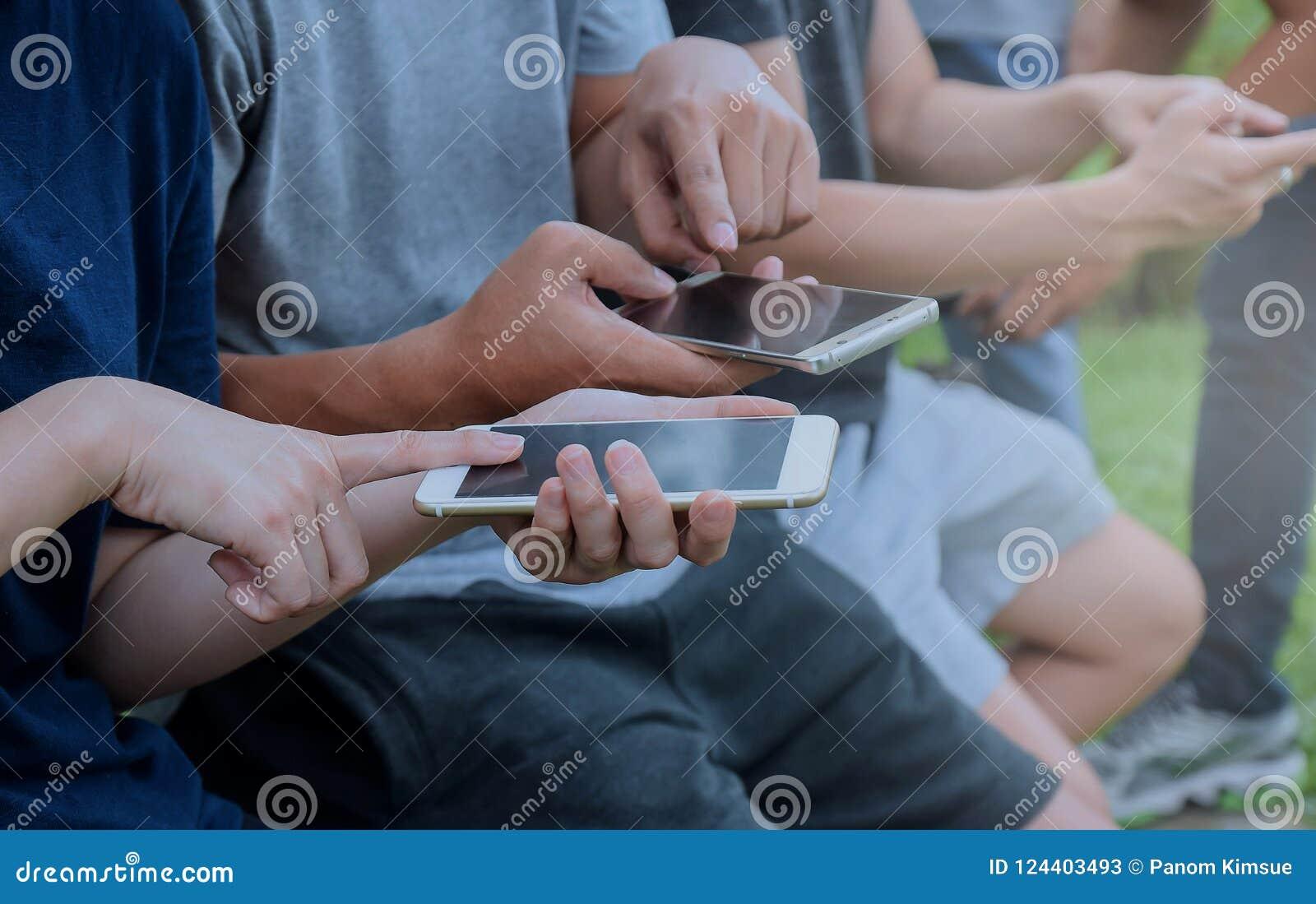 Närbild av smartphones i händerna av kvinnor som utomhus sitter Mötevänner Flickor som använder digitala grejer