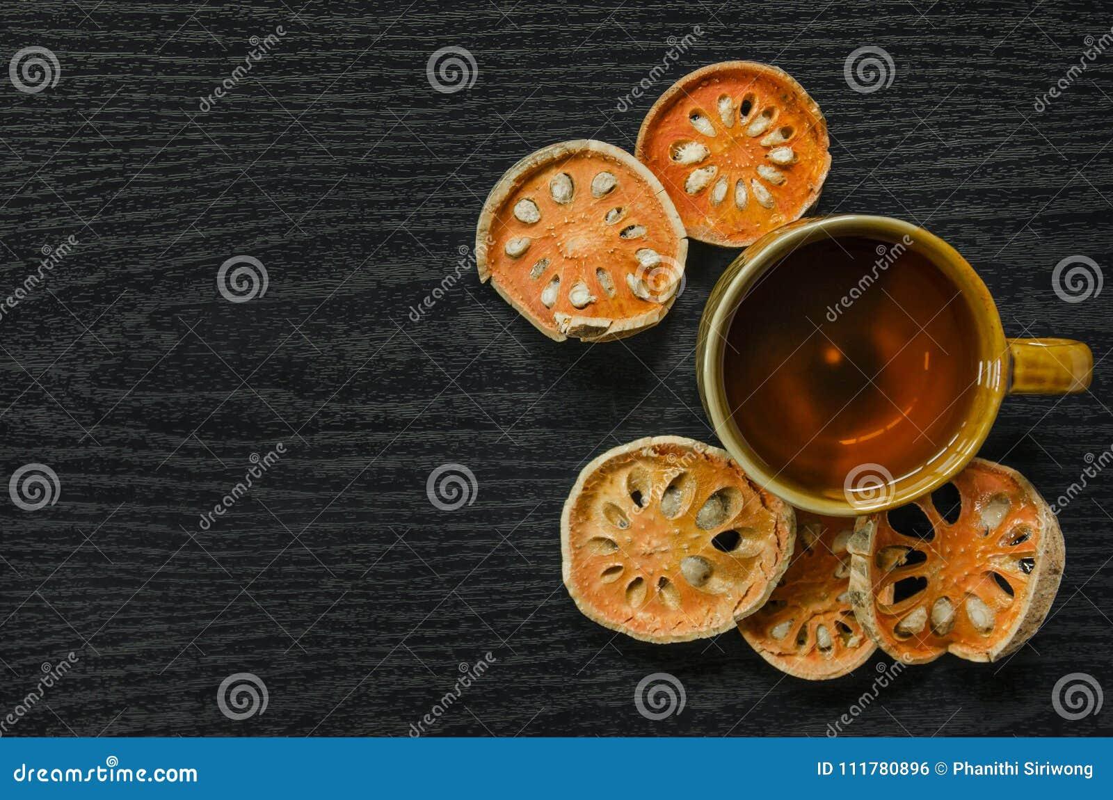 Närbild av torr och glass te för bael och baelfruktsaft på trägolvet