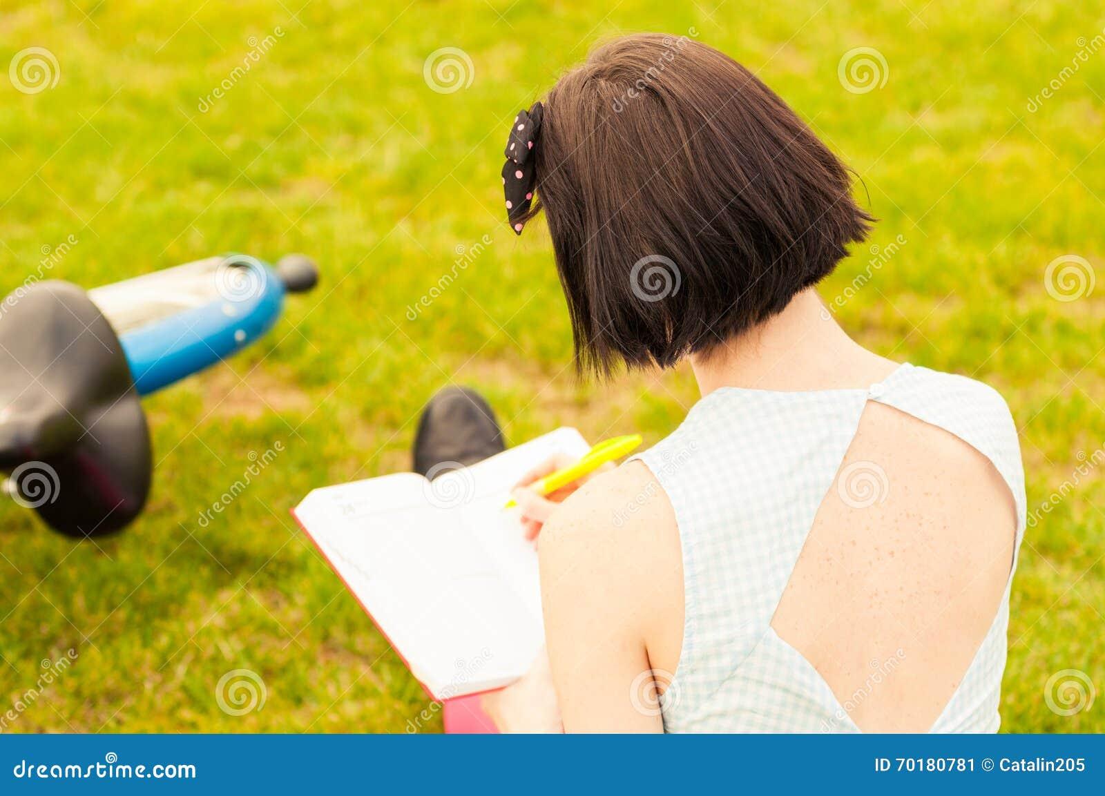 Närbild av ung kvinnligbaksida med cykeln och en bok