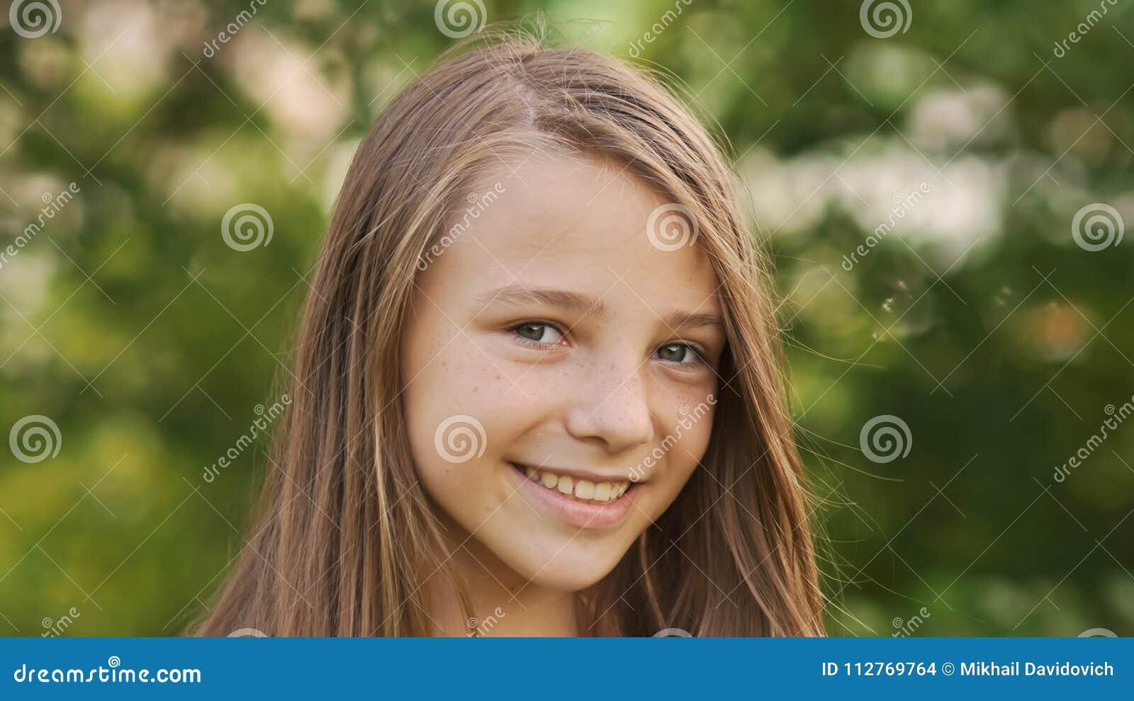 Närbild för flickatonåringframsida med generade fräknar och roligt posera och att spela med hans hår