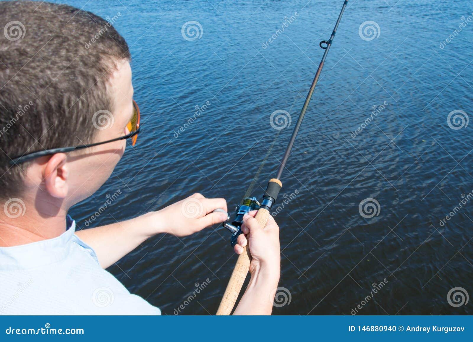 Närbild mot sjön, en man i gula exponeringsglas som rymmer en metspö för att fiska