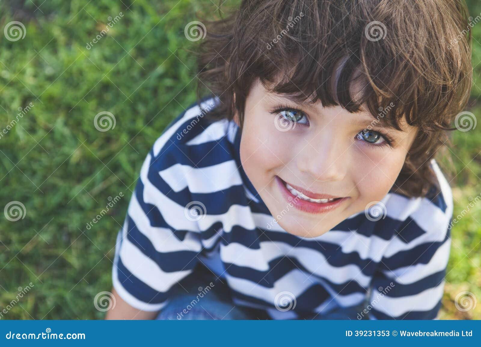 Närbilden av en gullig pojke som ler på, parkerar