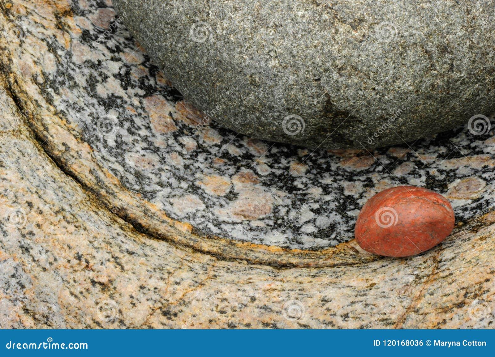 Närbilden av ett slätt rödaktigt vaggar mot färgad annan texturerat vaggar