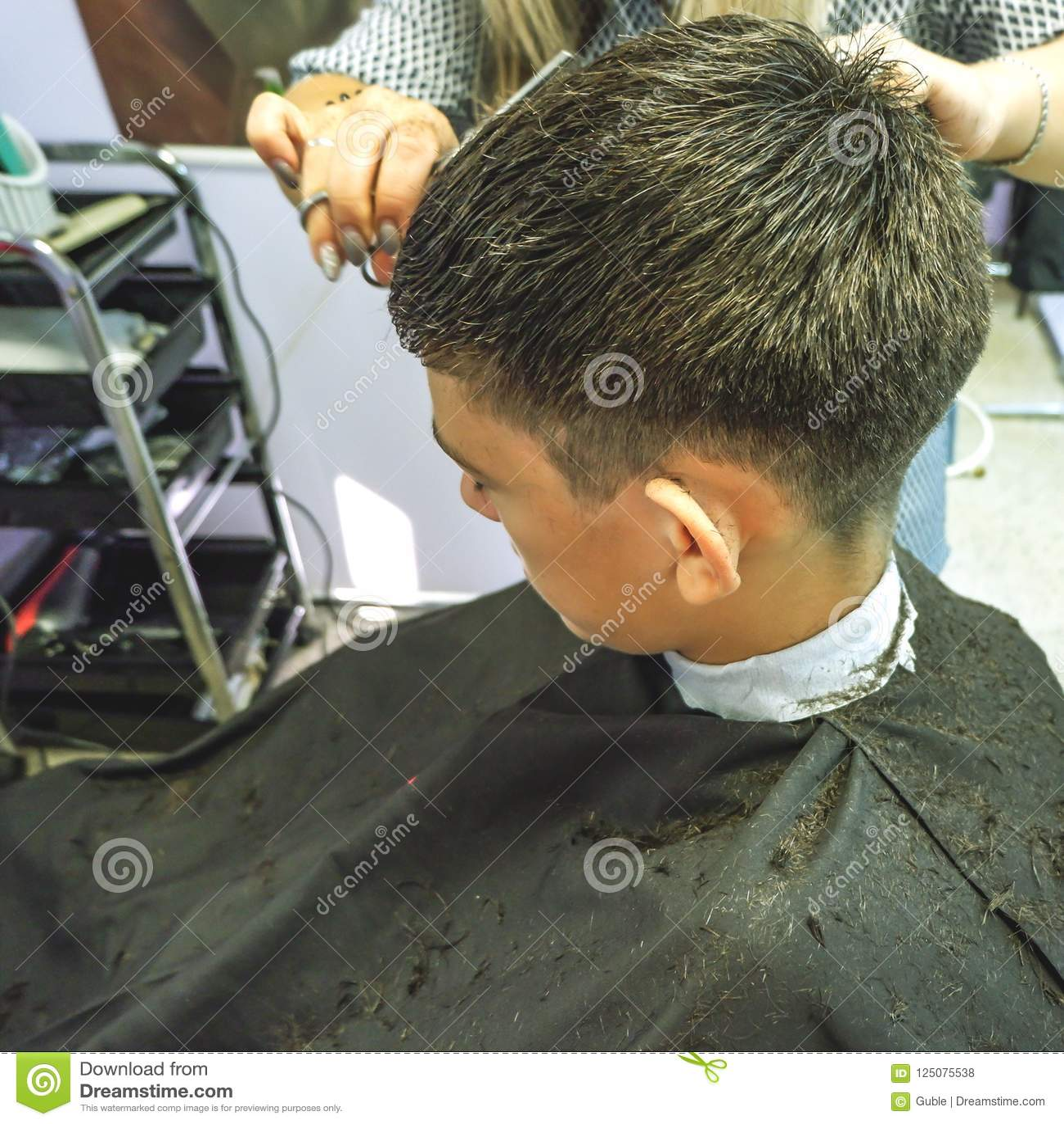 _ Närbilden av frisyrer tonåringen, förlage gör hårfrisyren i barberare för att shoppa