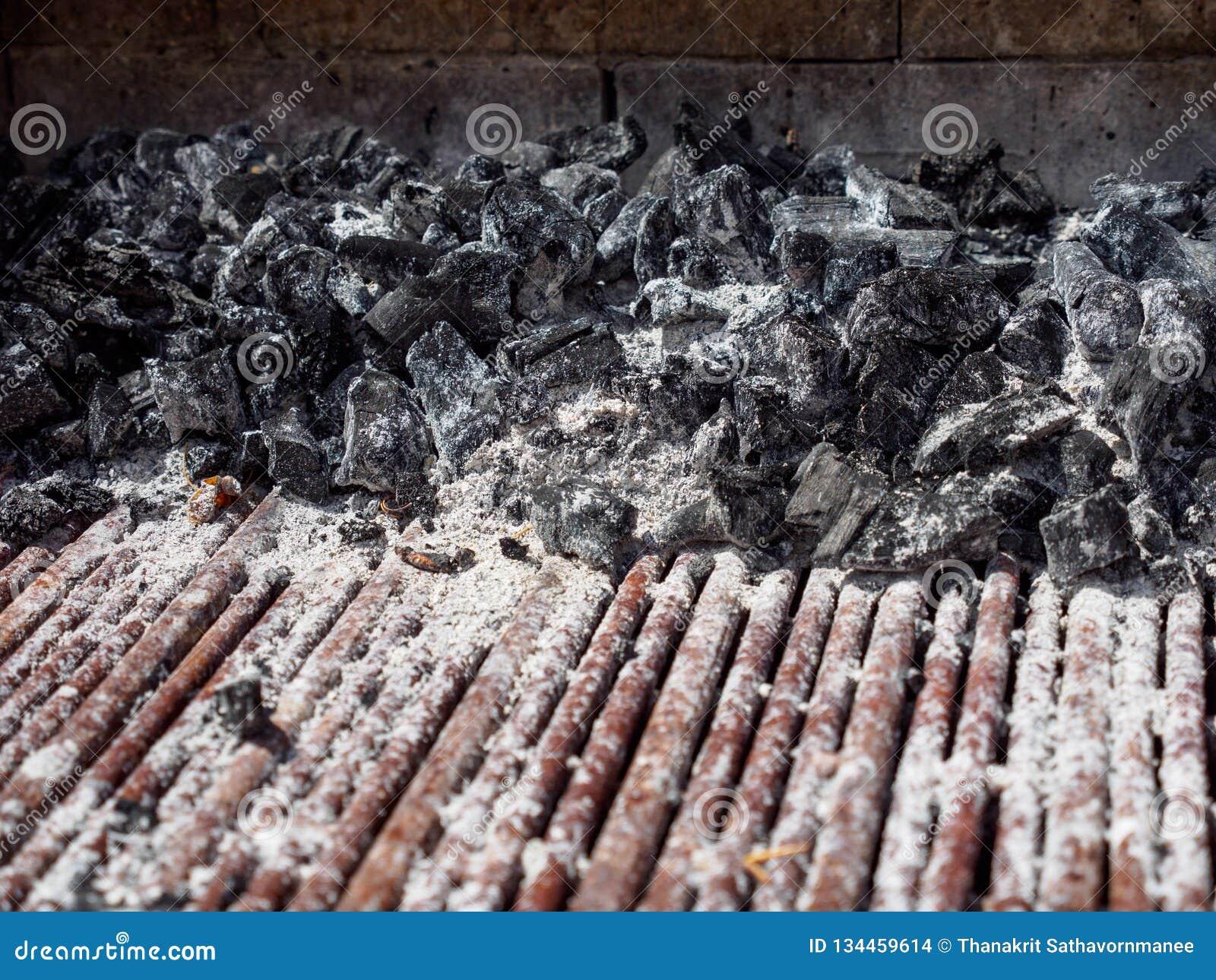 Närbilden av kol klumpa sig och metallkuggen som täckas med askaen