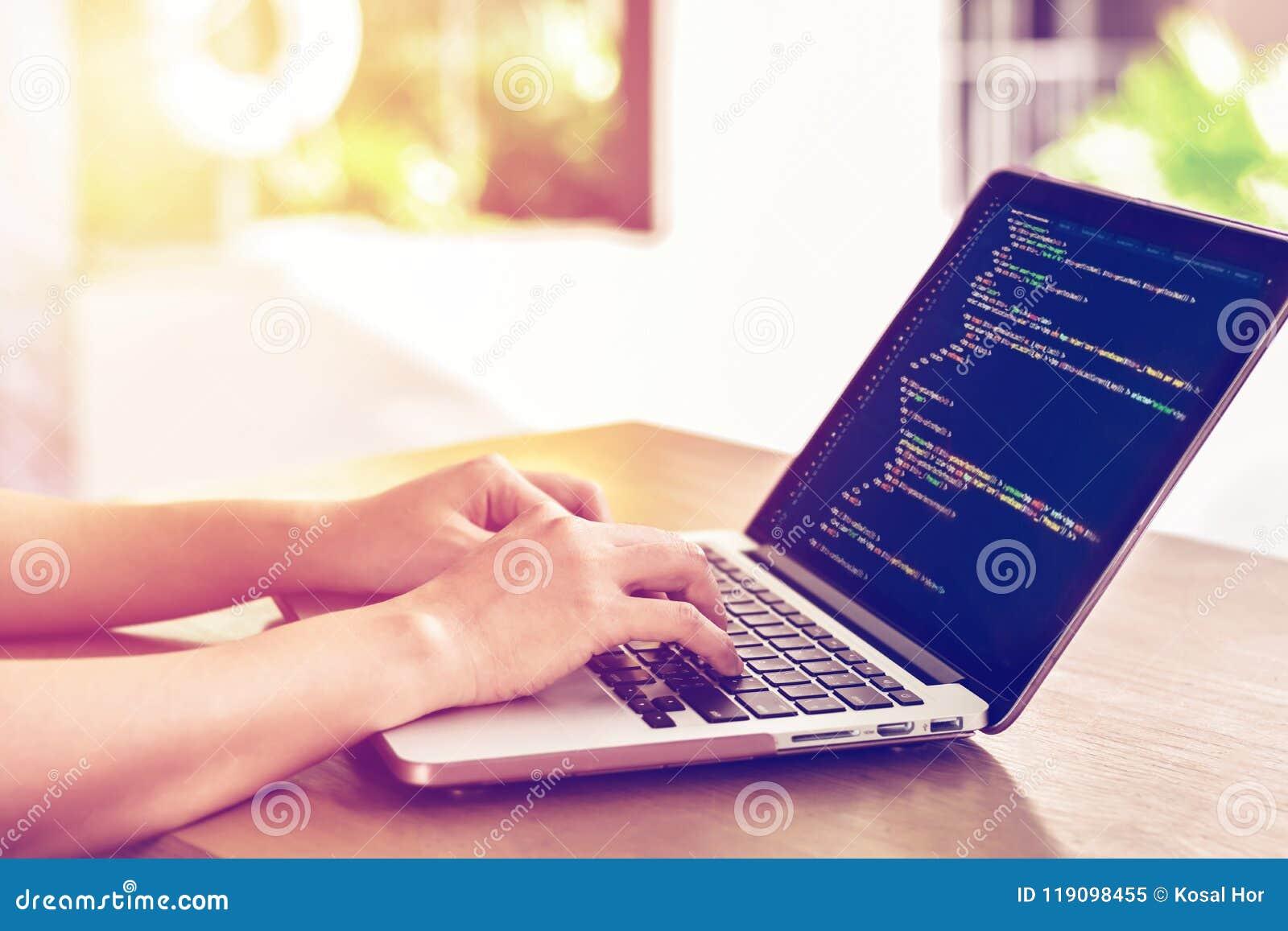 Närbilden av programmerare` s räcker arbete på källkoder över en bärbar dator utomhus