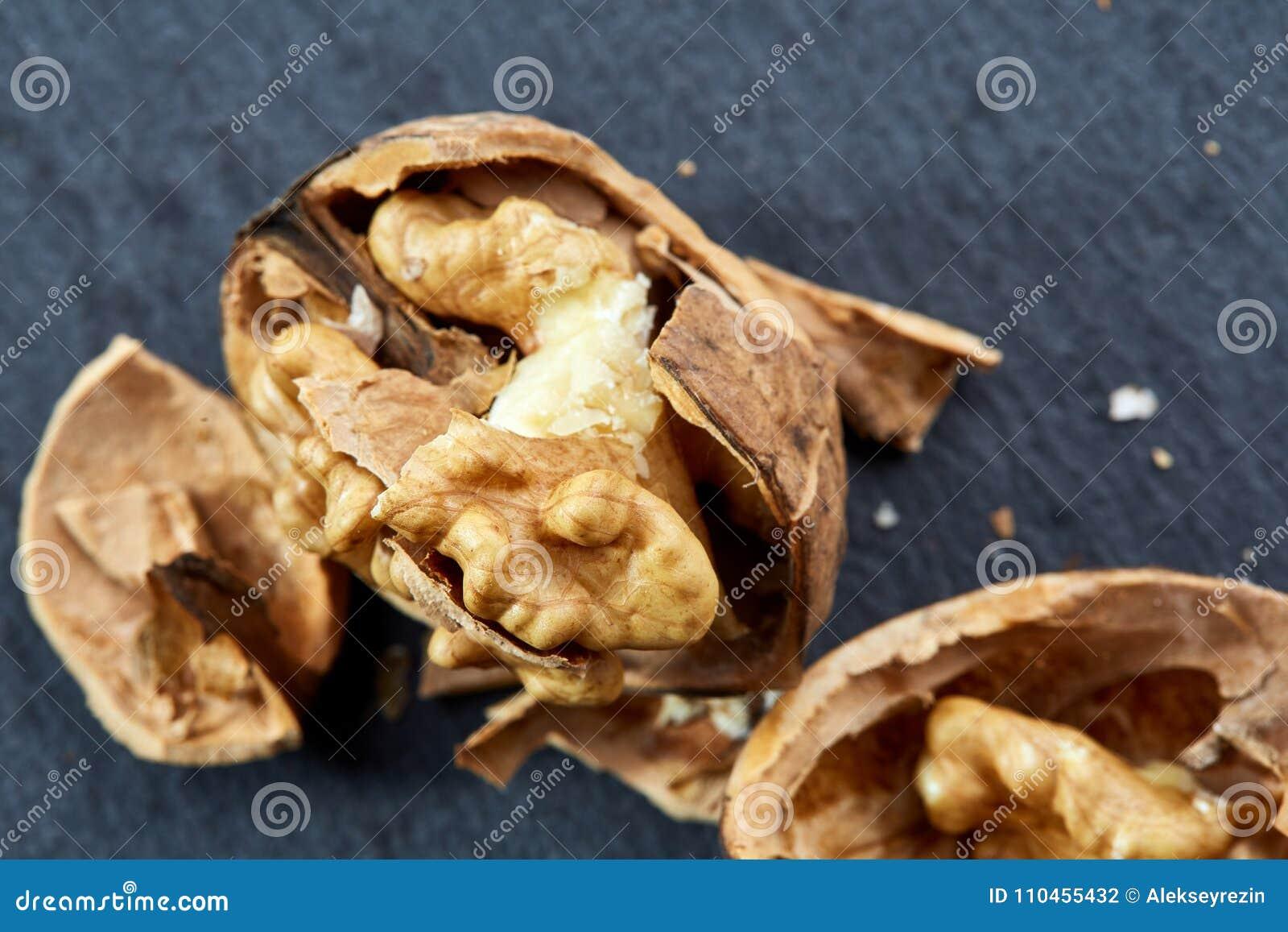 Närbilden för bästa sikt sköt av spruckna valnötter på mörk bakgrund, grunt djup av fältet, makro