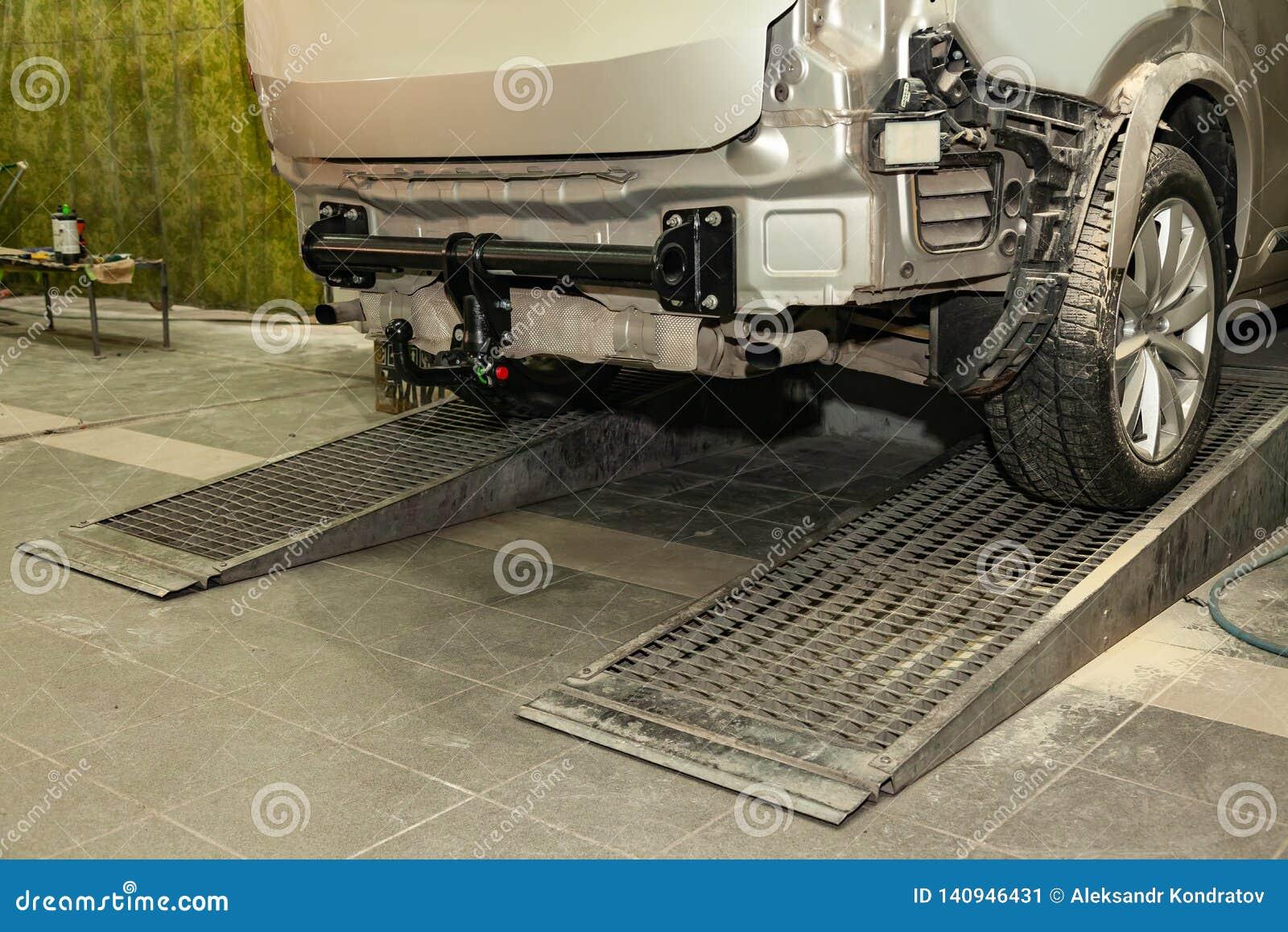 Närbilden på en ny svart släphake som installeras på en modern bil med en borttagen beiga-färgad stötdämpare i en medelreparation