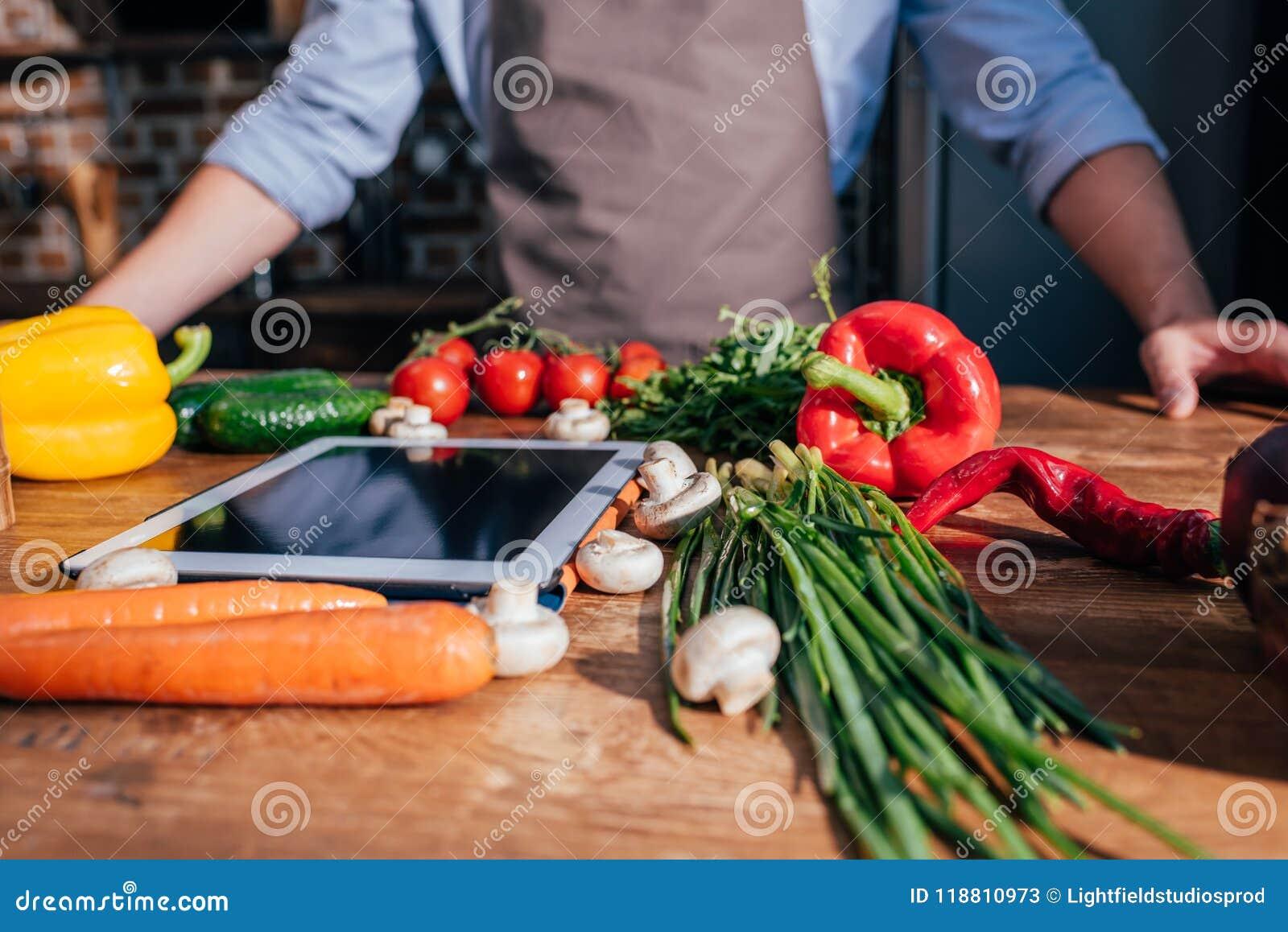 Närbilden sköt av matlagning för ung man med minnestavlan
