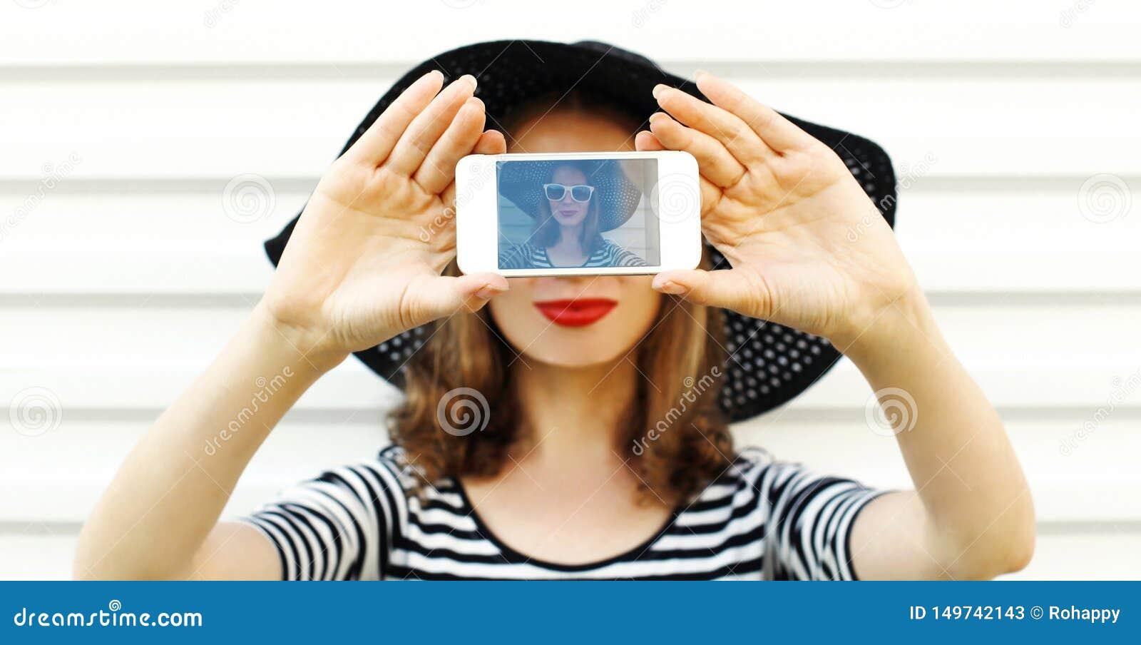 Närbildkvinna som tar selfiebilden vid telefonen på den vita väggen