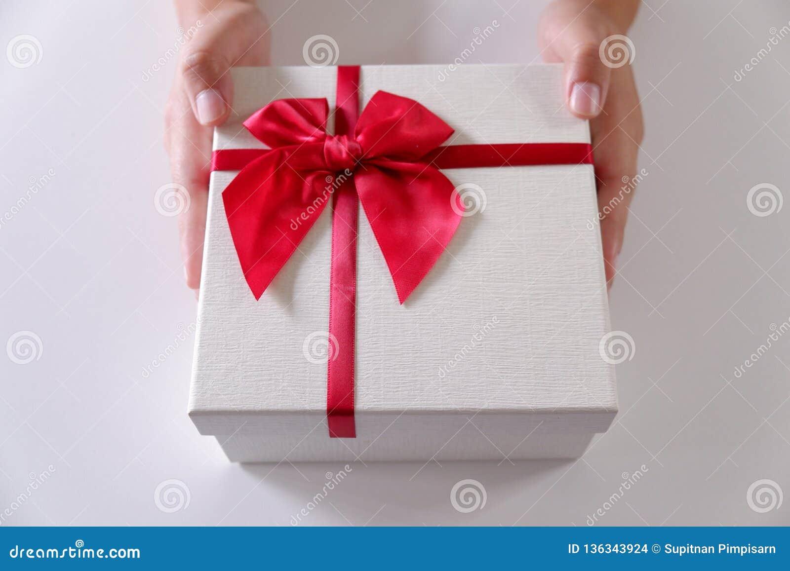Närbildkvinnahänder som överför den vita gåvaasken med det röda bandet på vit bakgrund