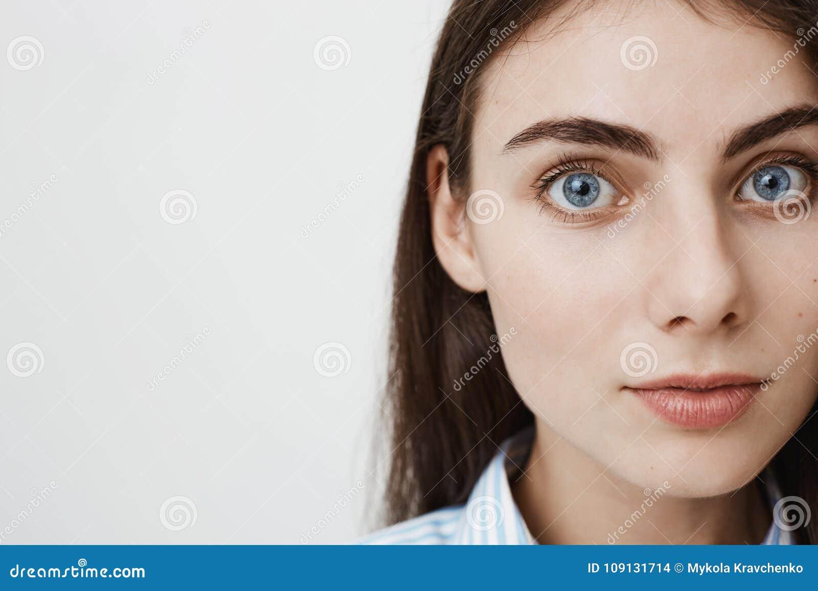 Närbildsidostående av den försiktiga nätta europeiska studenten som ser kameran, medan stå mot grå bakgrund Kvinna