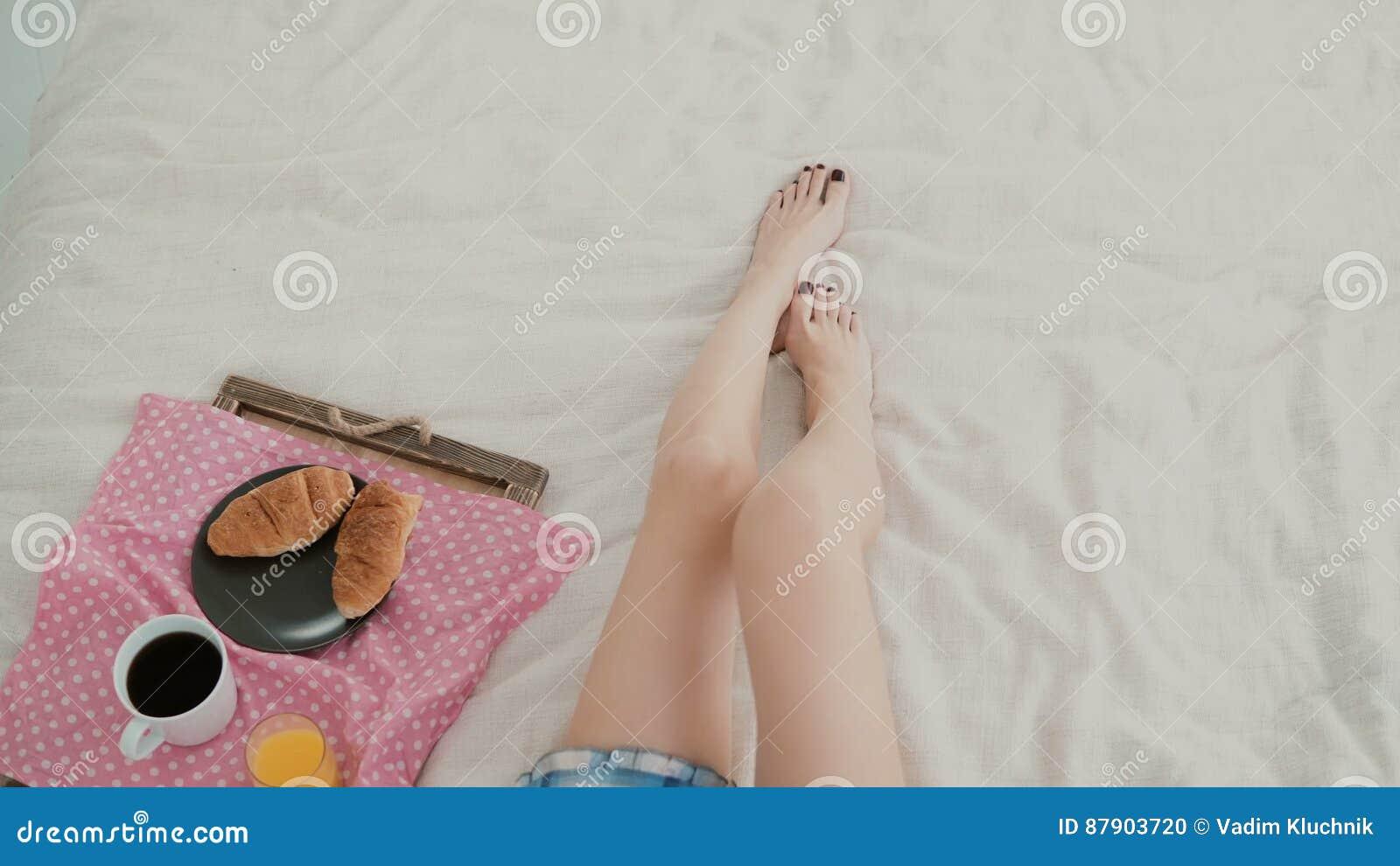 Närbildsikt av foten för kvinna s Ung flicka som ligger på sängen och att ha frukosten i vardagsrum