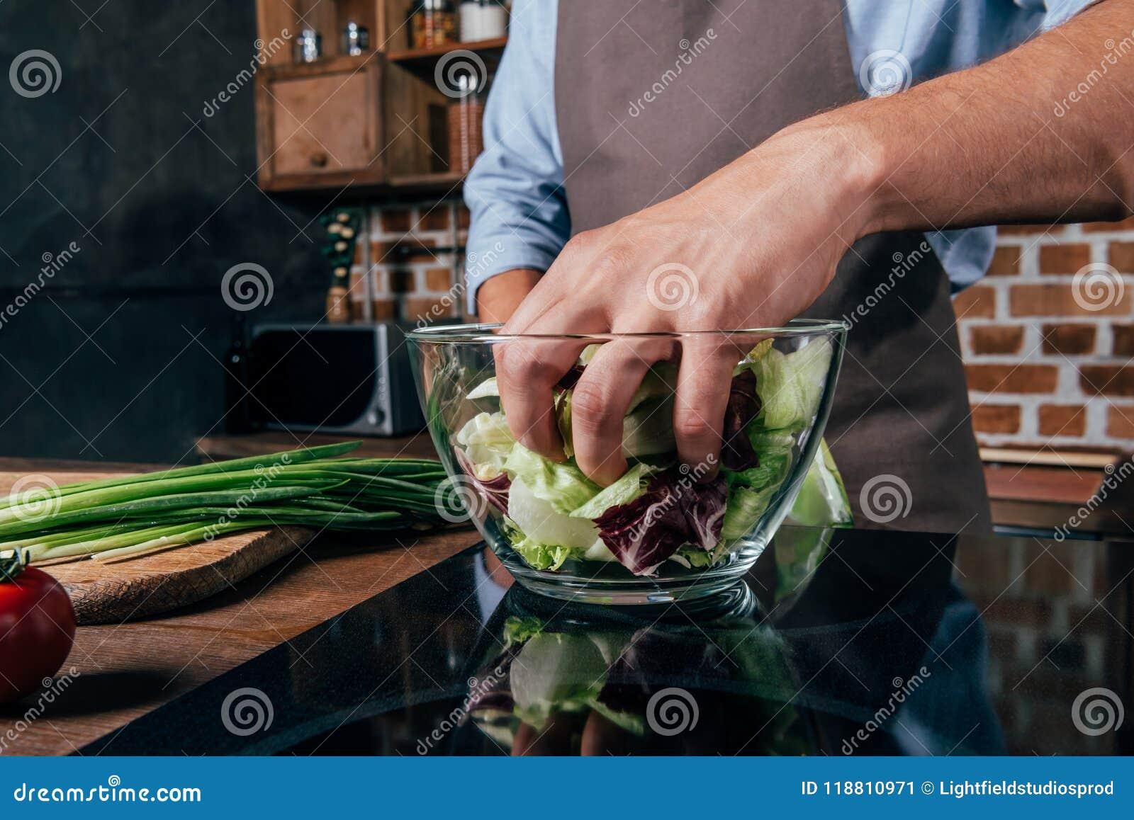 Närbildskott av blandande sallad för man med händer