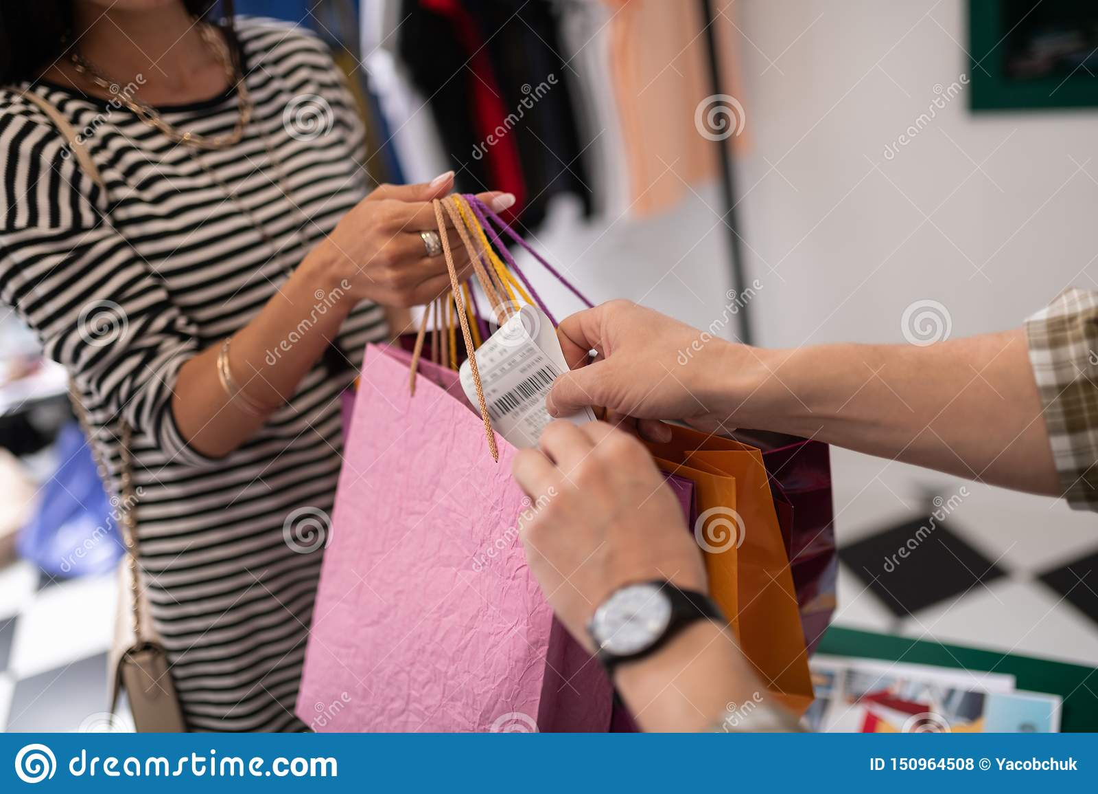 Närbildskott av kassörskan som sätter ett kvitto till den shoppa packen