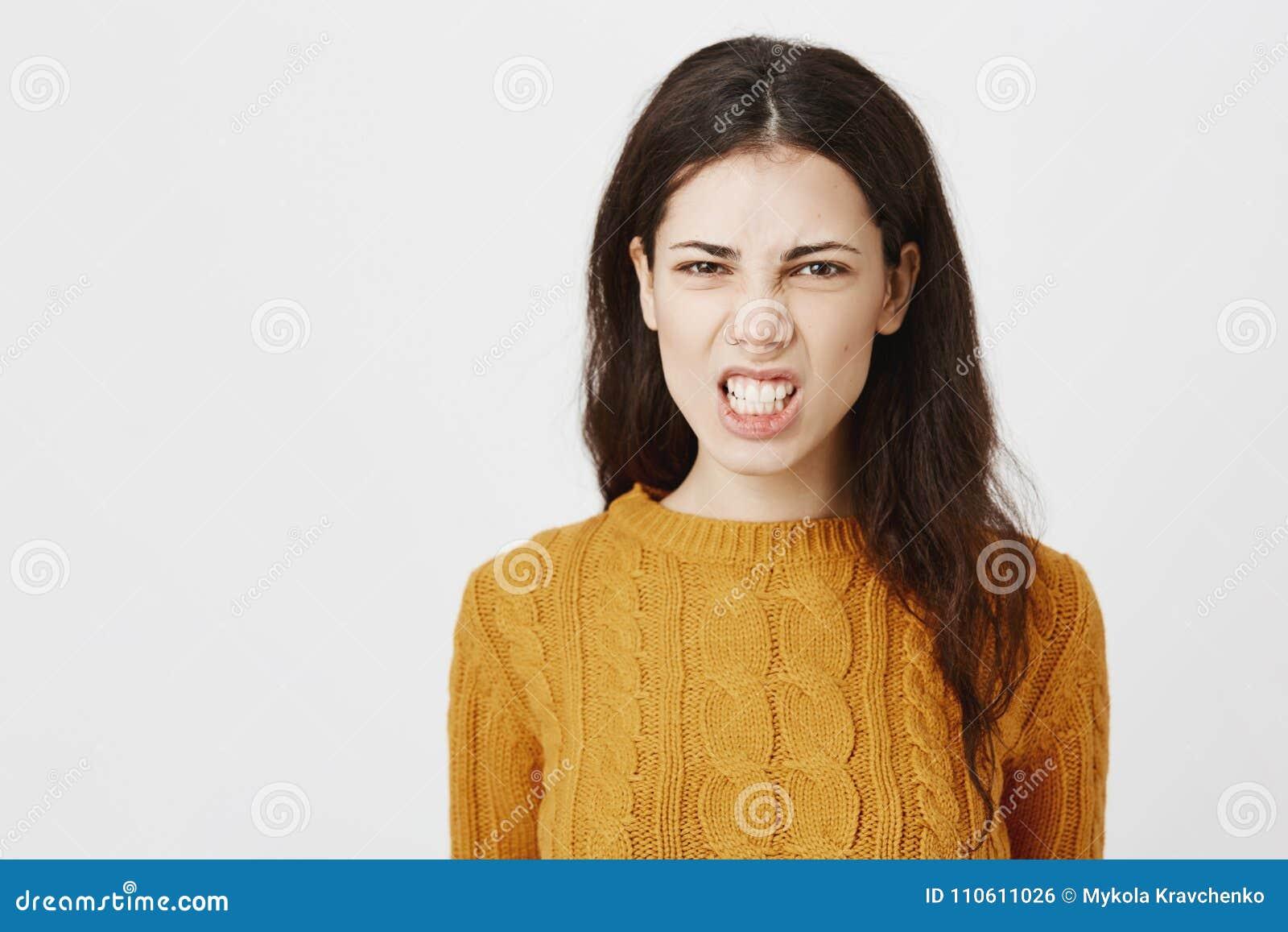 Närbildstående av den irriterade tokiga europeiska kvinnan som grinar och skelar på kameran och att uttrycka ilska och anseende ö