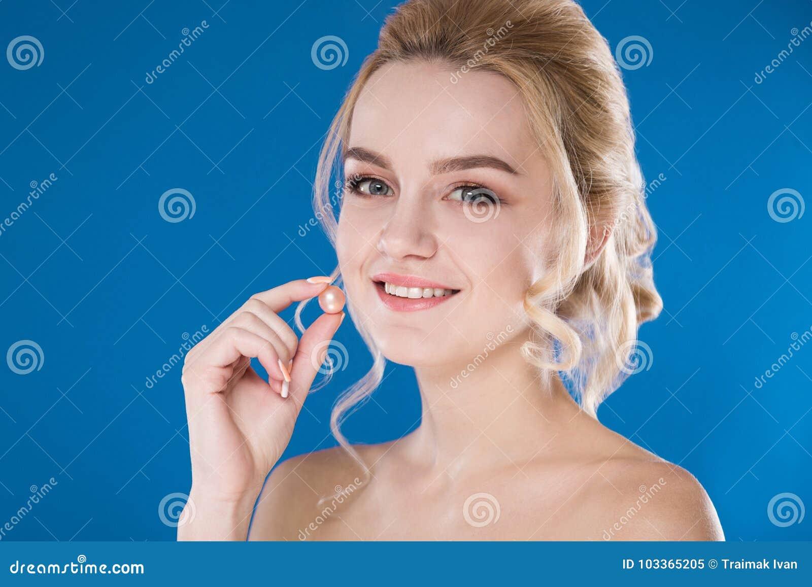 Närbildstående av en ung flicka på en blå bakgrund