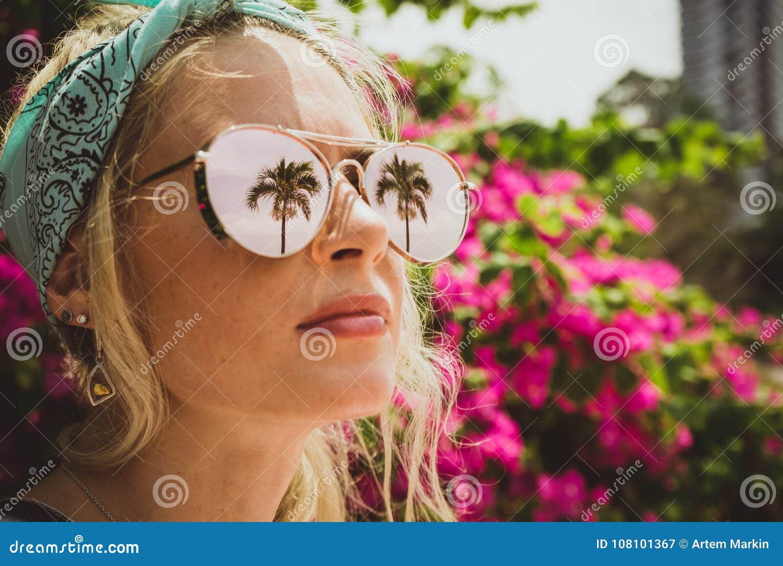 Närbildståenden av en ung härlig flicka i exponeringsglas med reflexion av tropiskt gömma i handflatan Sommar vilar den moderna t