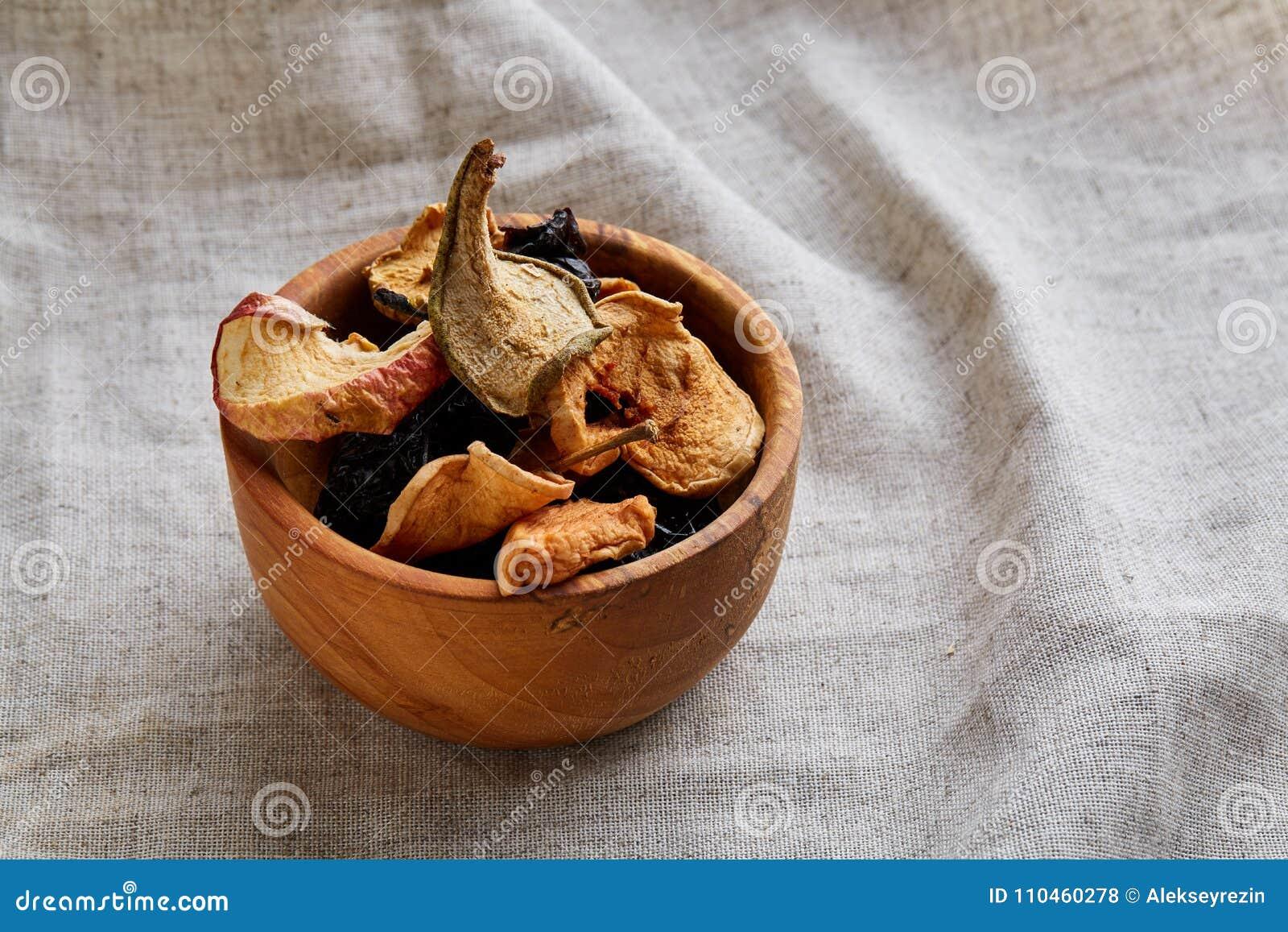 Närbildträbunke med torkade frukter på en ljus bordduk