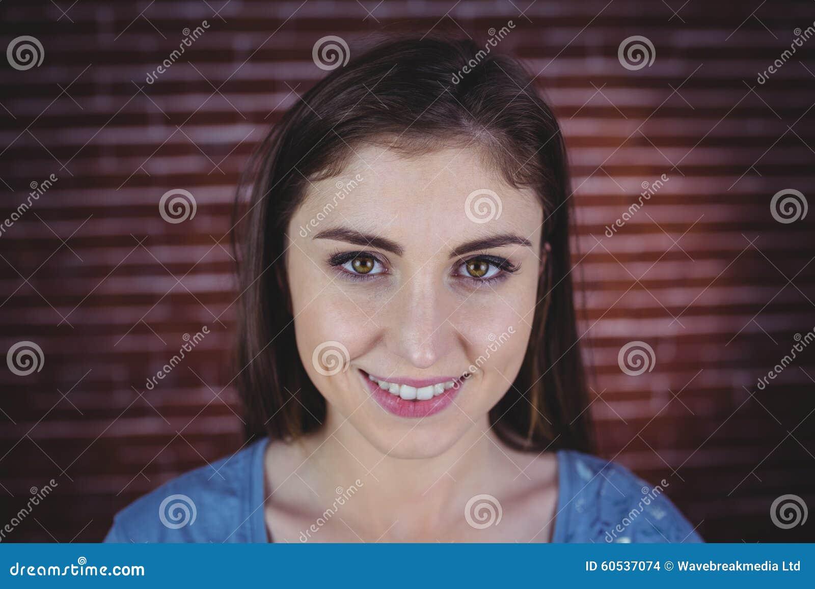 Nätt brunett som ler på kameran