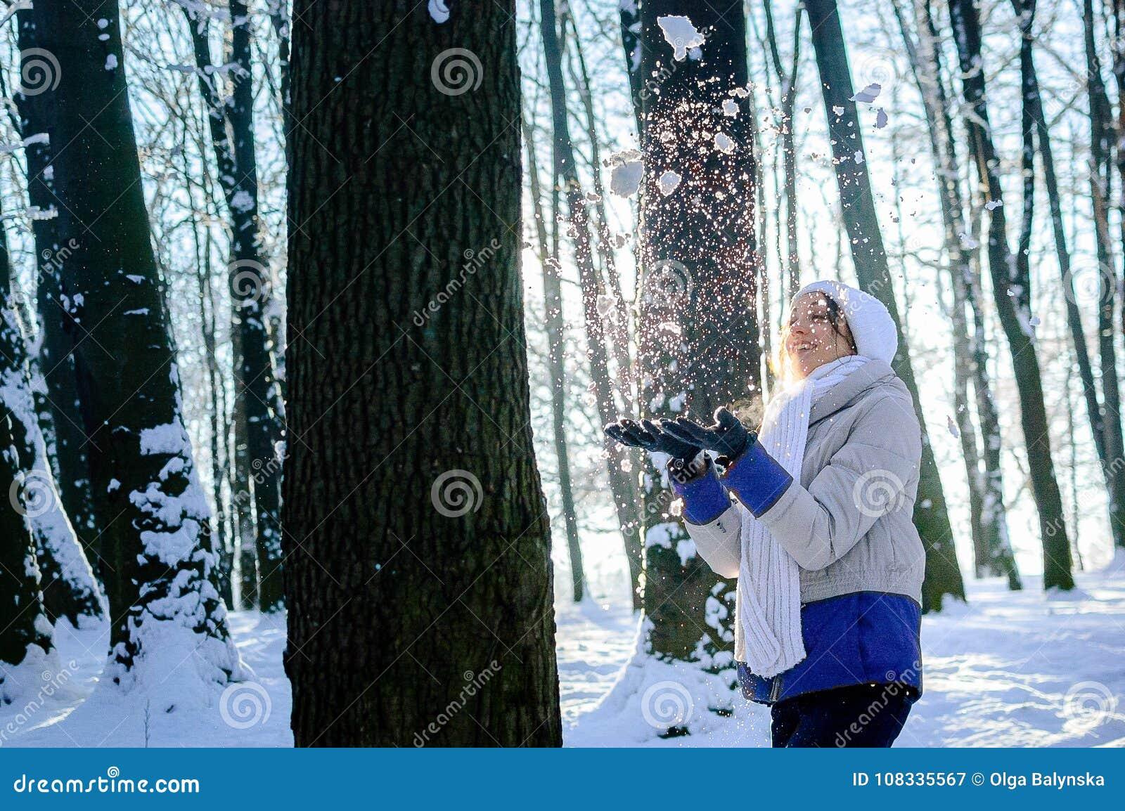 Nätt flicka i vit hatt- och halsdukslagsnö från hennes händer under soligt väder i vinter