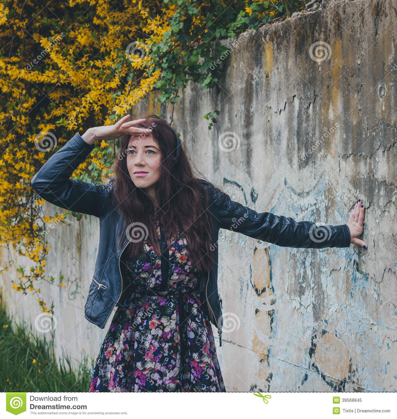 Nätt flicka med lång hårbenägenhet mot en betongvägg