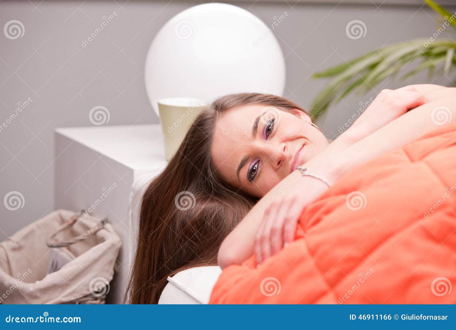 Nätt flicka som går att sova på hennes soffa