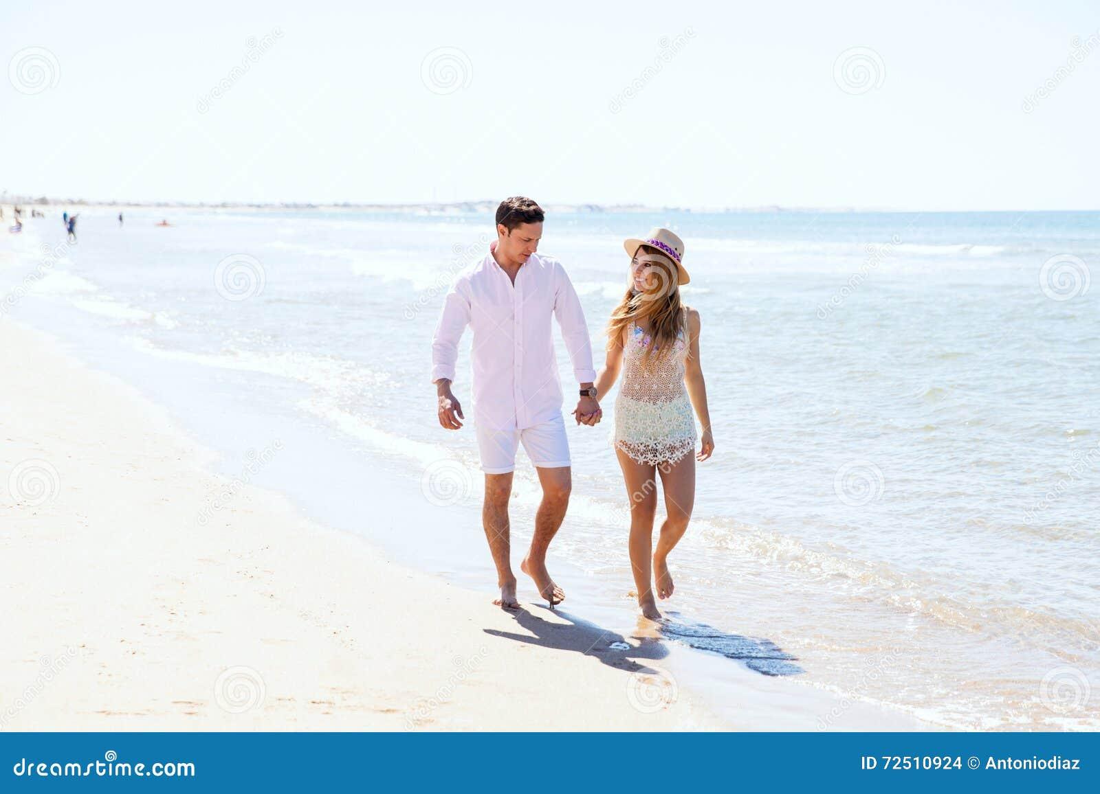 Nätt flicka som går med hennes pojkvän på stranden