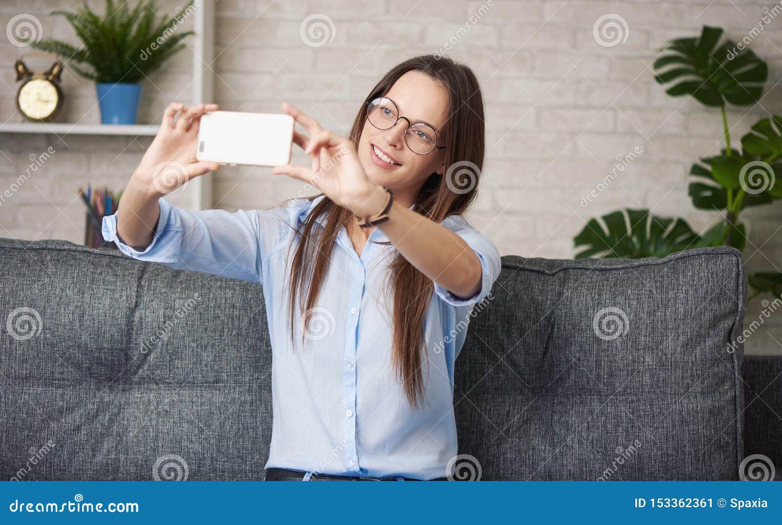 Nätt flicka som gör selfie, medan sitta på en soffa