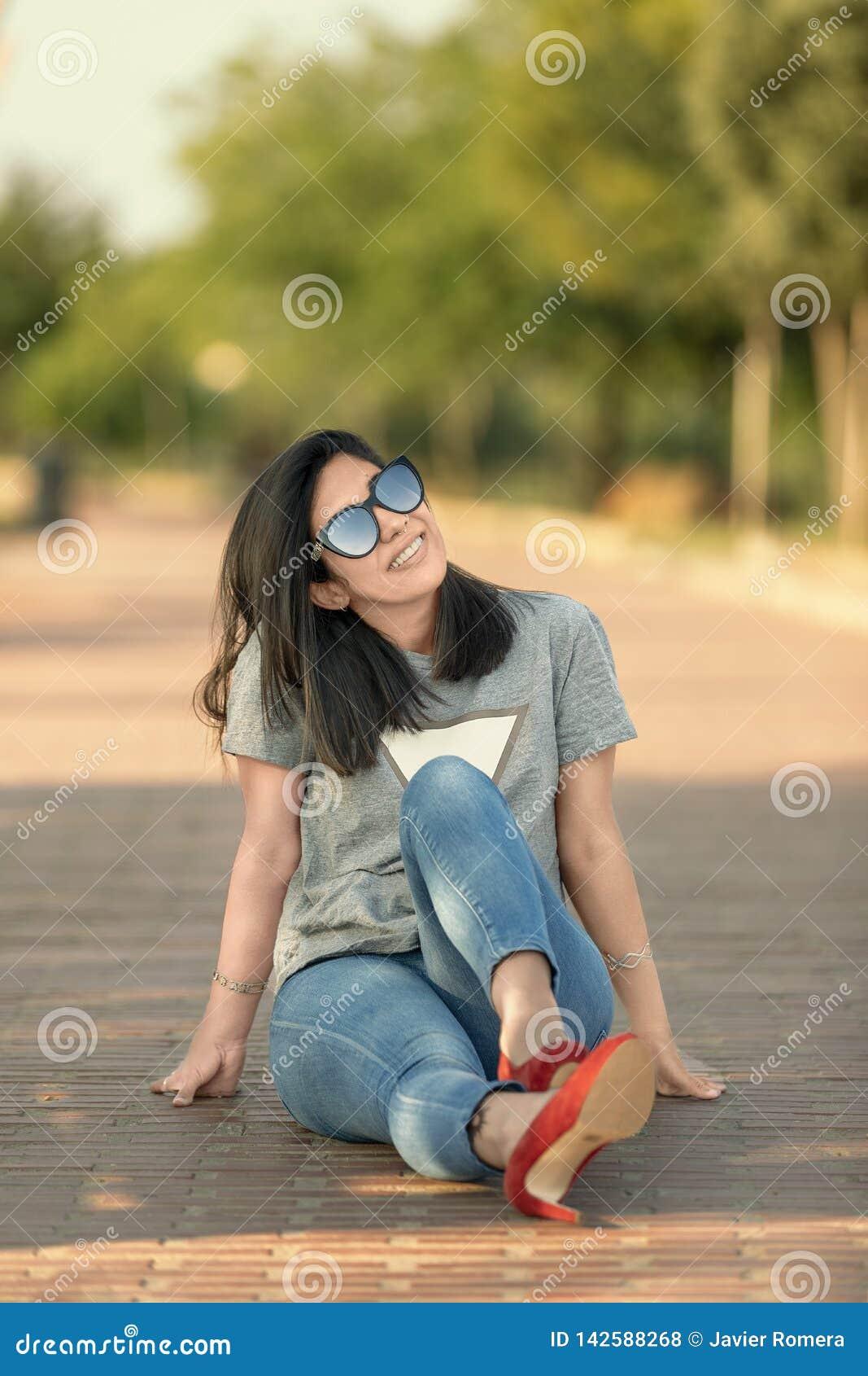 Nätt flicka som sitter på golvet som ser upp