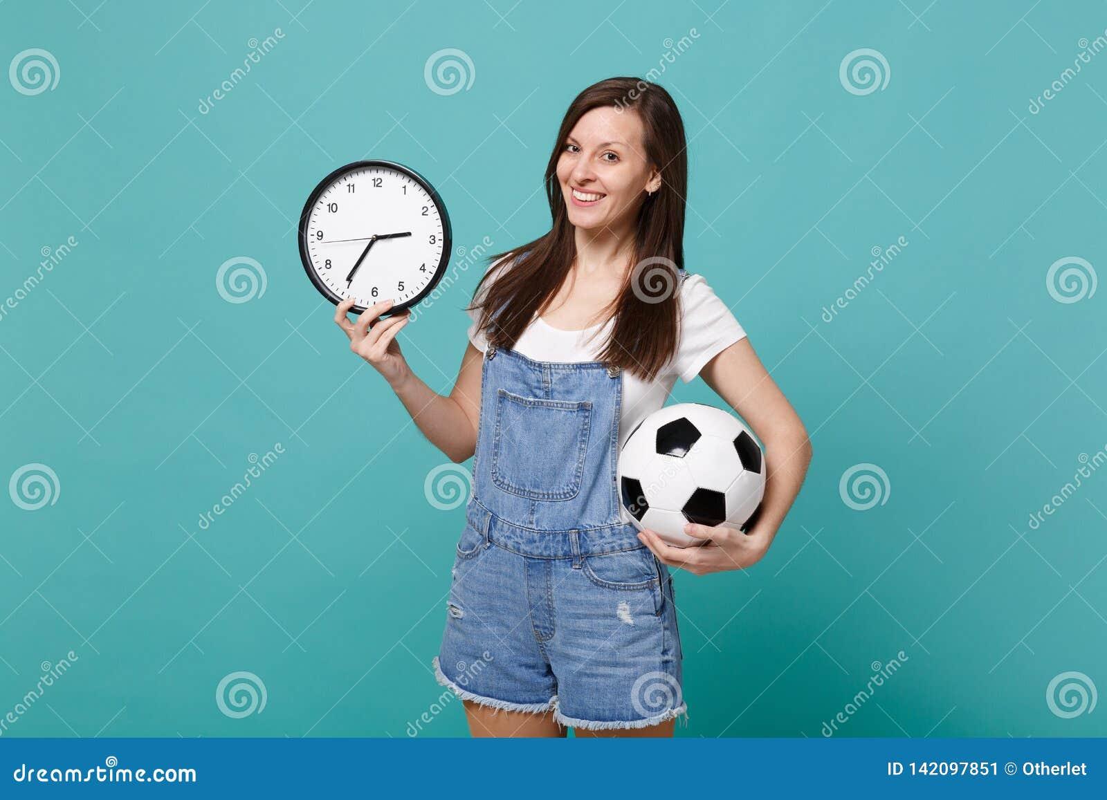 Nätt fotbollsfanjubel för ung kvinna upp, favorit- lag för service med fotbollbollen, rund klocka som isoleras på blå turkos