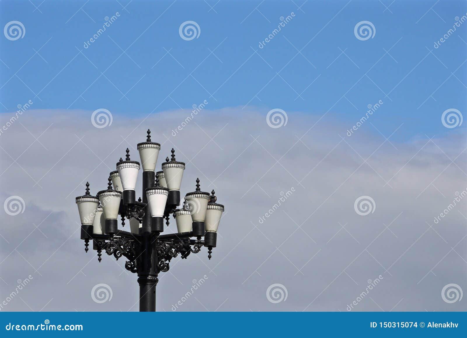 Nätt gatalampa med många exponeringsglasräkningar på bakgrund av blå himmel