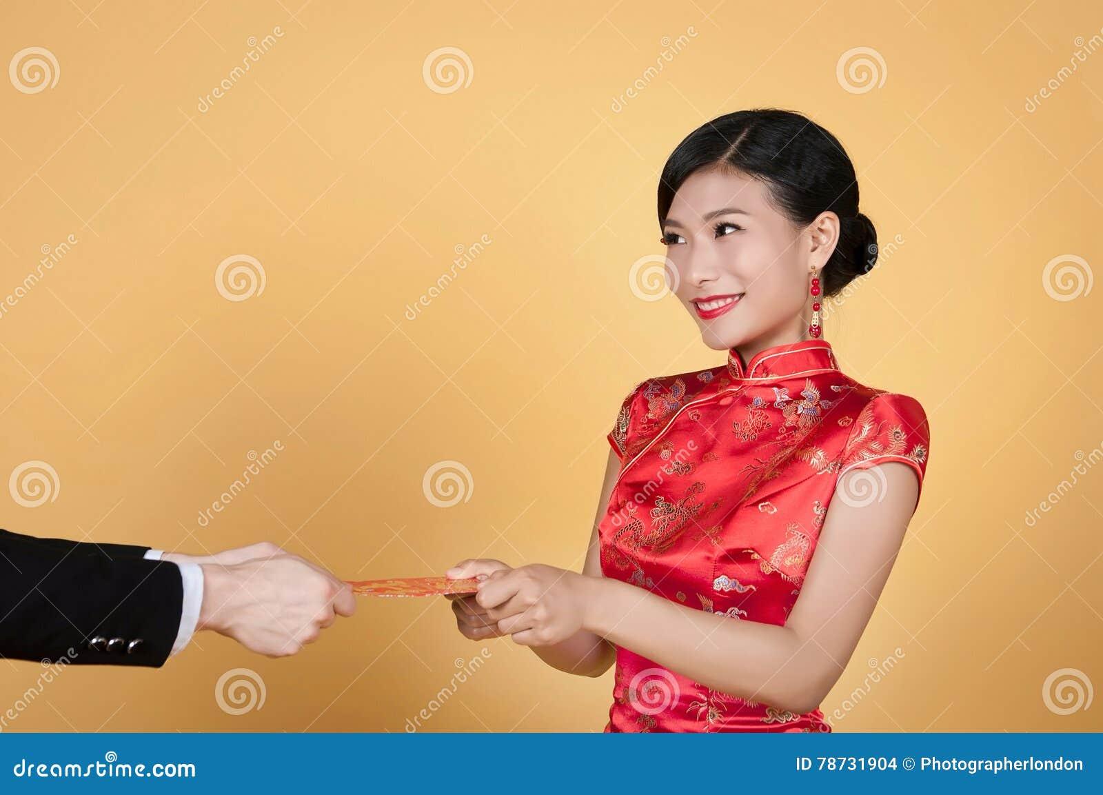 Nätt kinesisk ung kvinna som mottar det röda facket för lyckligt kinesiskt nytt år