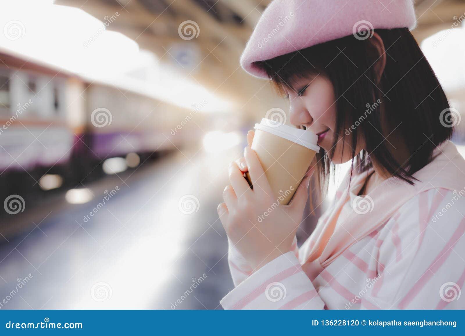 Nätt kopp för kvinnahållkaffe, varmt svart kaffe för drink i morgon under att vänta drevet på drevstationen