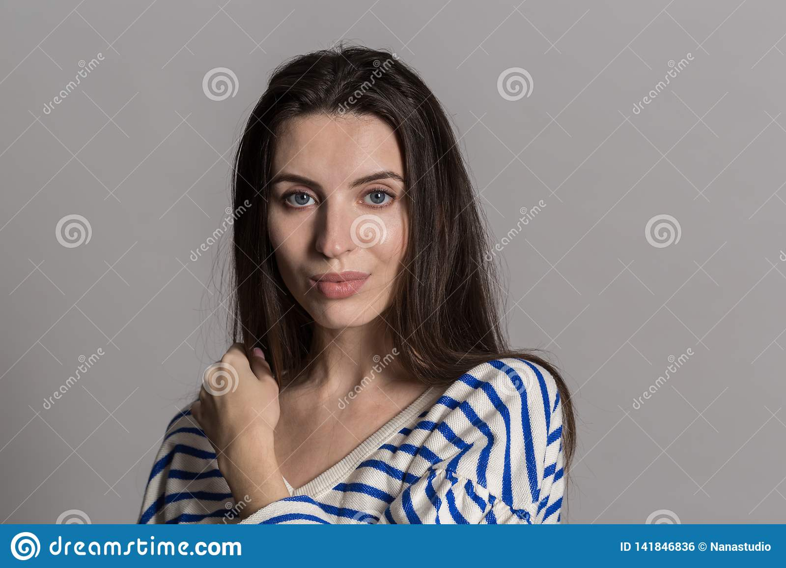 Nätt kvinna med fluffigt hår, påklädd tillfälligt mot en grå studiovägg