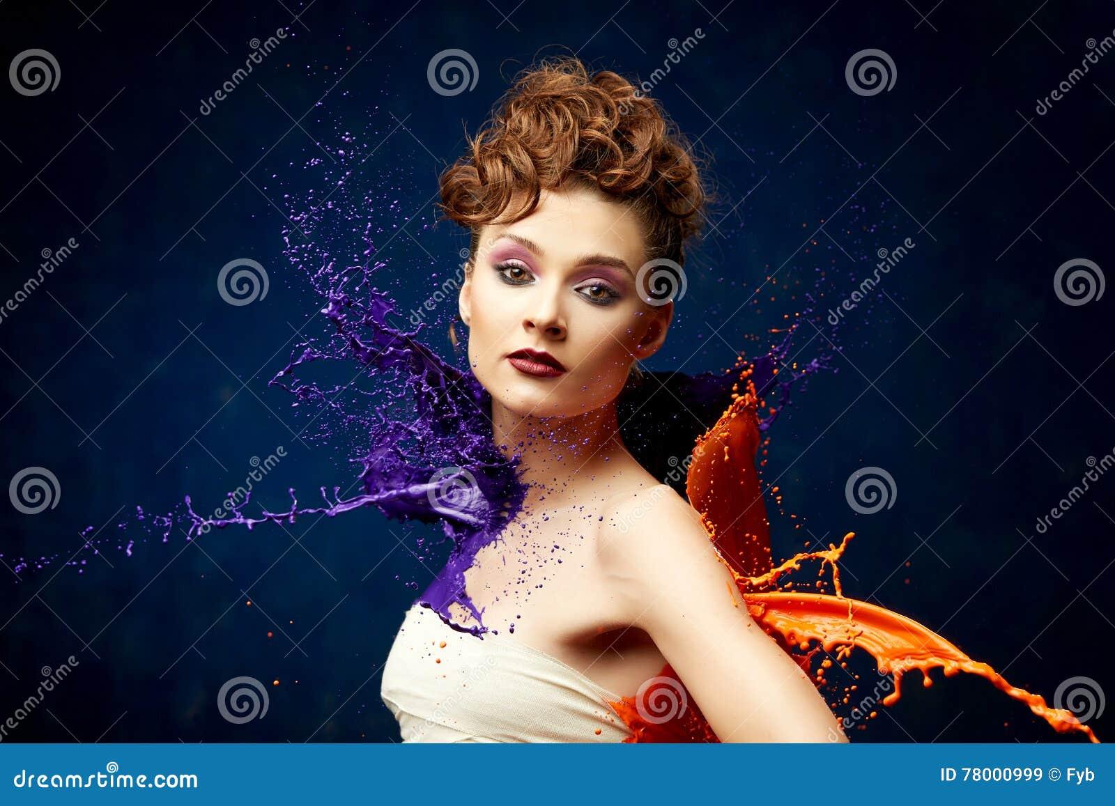 Nätt kvinna som slås av målarfärg