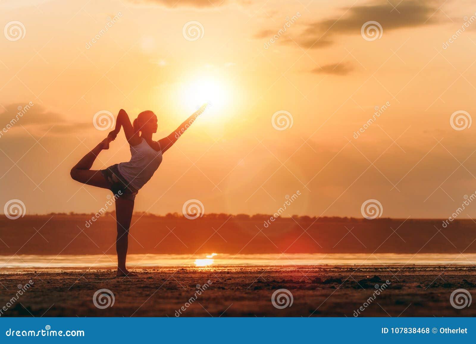 Nätt kvinna som utomhus gör yoga på solnedgången