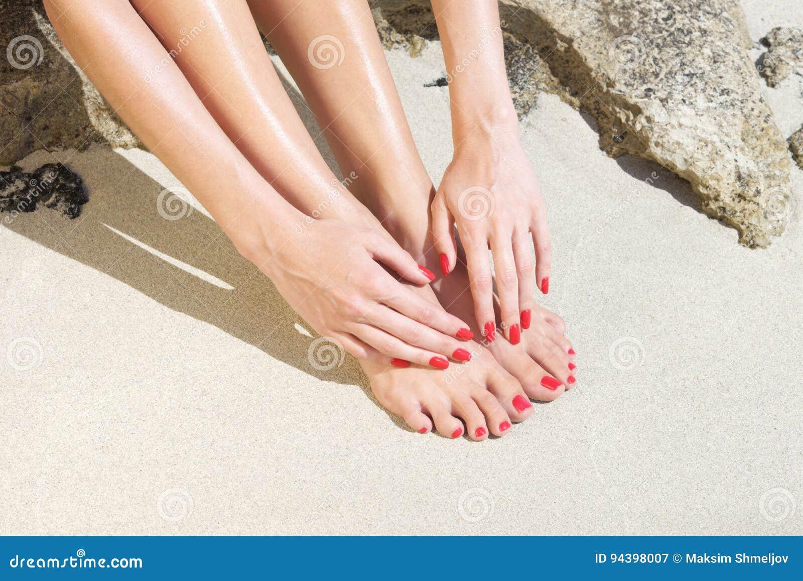Nätt kvinnafot med röd manikyr och pedikyr: koppla av på sand