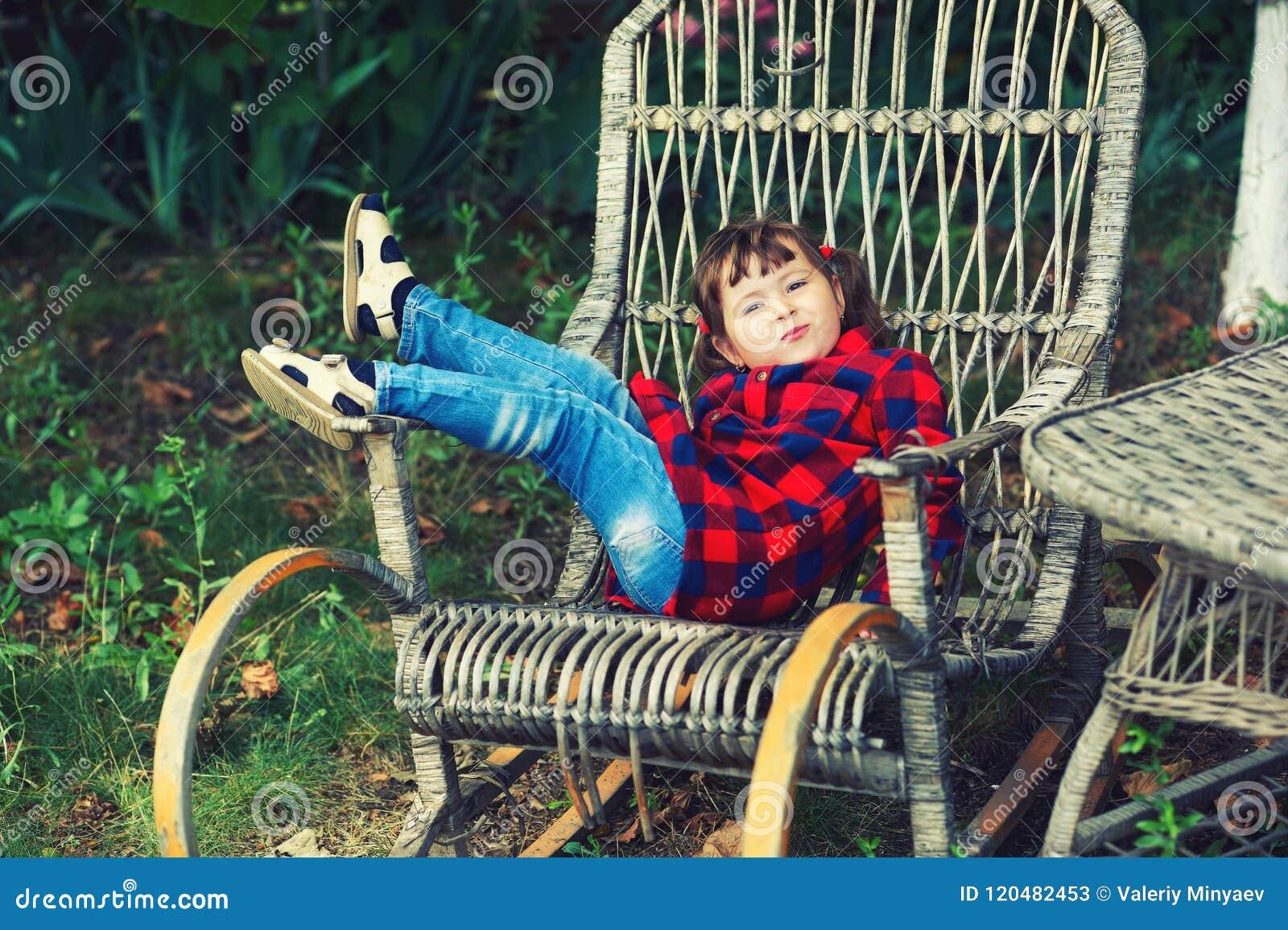 Nätt liten flicka i en stol i trädgården