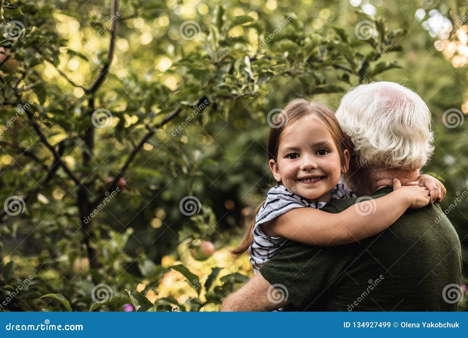Nätt liten flicka med hennes farfar i trädgård