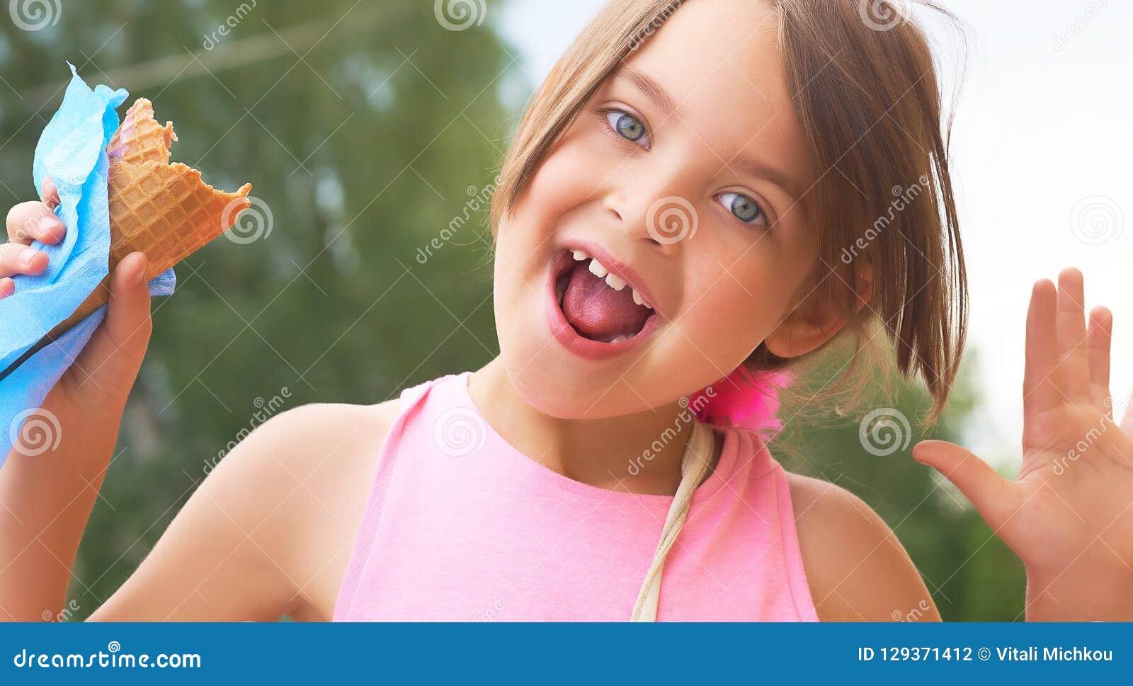 Nätt liten flicka som äter slicka stor glass i lyckligt skratta för dillandekotte på naturbakgrund