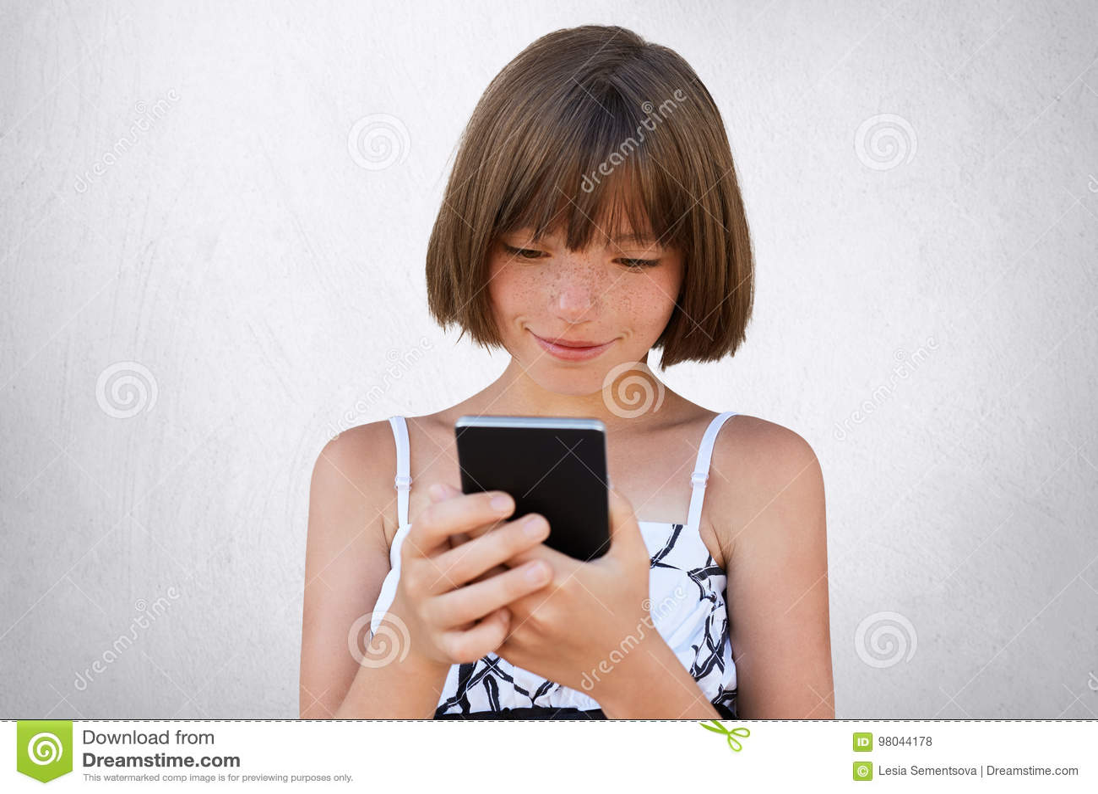 Nätt liten flicka som uppmärksamt ser in i hennes smarta telefon, medan hålla ögonen på tecknade filmer använda direktanslutet fr