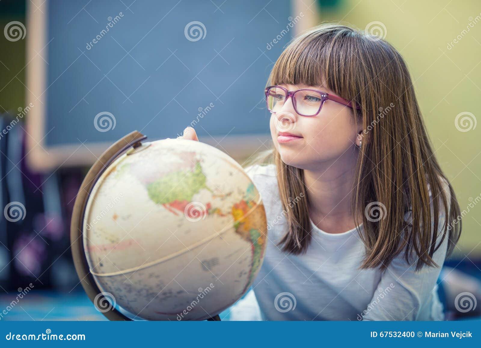 Nätt liten studentflicka som studerar geografi med jordklotet i barns rum