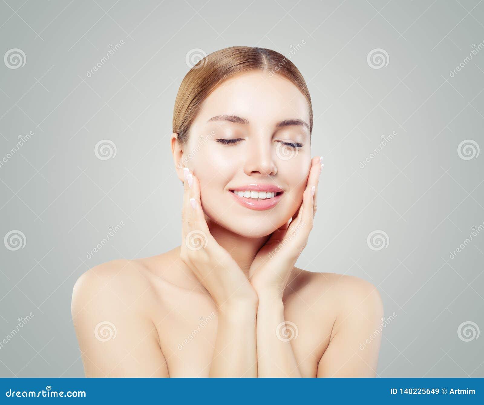 Nätt modellframsida Sund kvinna som kopplar av och ler på vit bakgrund, begrepp för hudomsorg