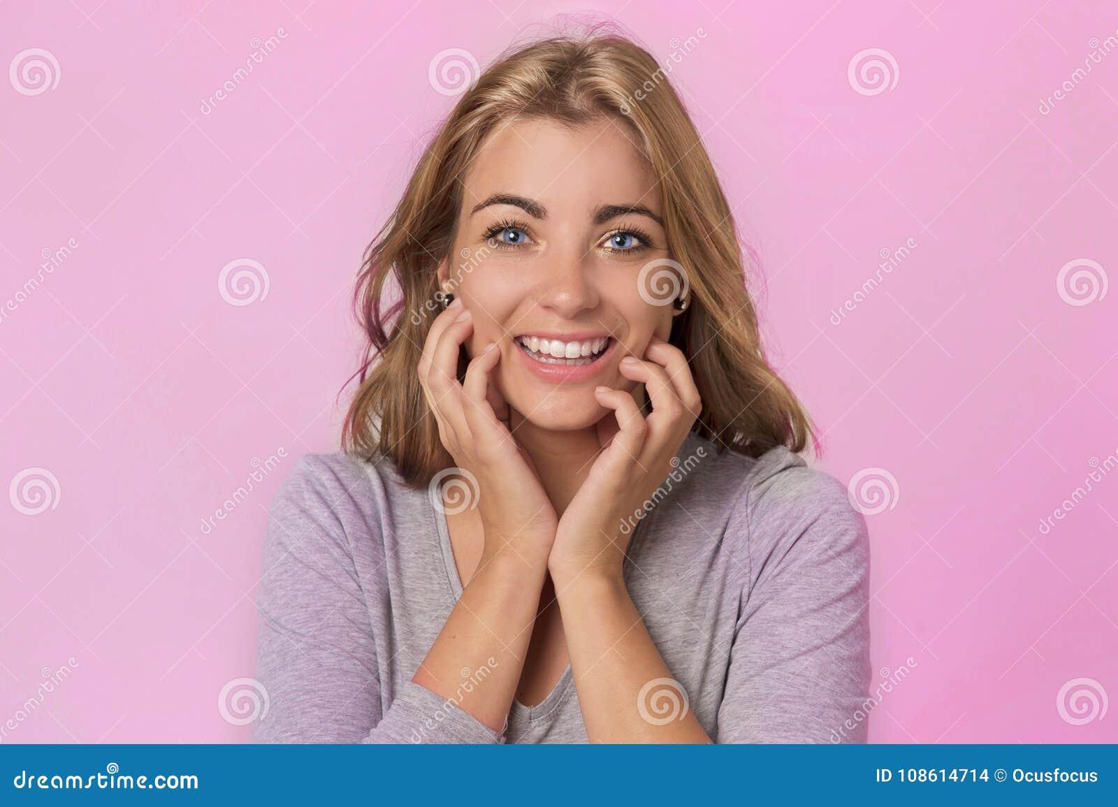 Nätt och attraktiv blond Caucasian flicka med härliga blåa ögon på hennes upphetsade 20-tal och lyckligt le som är gladlynt i söt