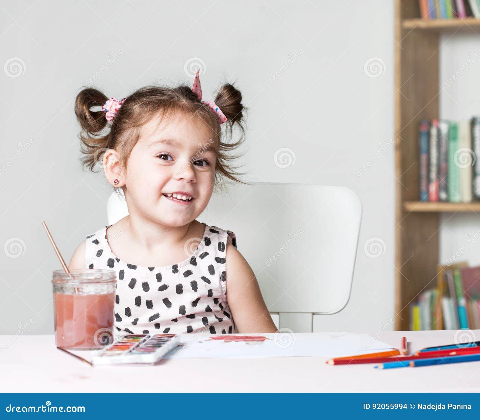 Nätt och gullig liten flickamålningbild med vattenfärgen i studio Begrepp av utbildningsprocessen
