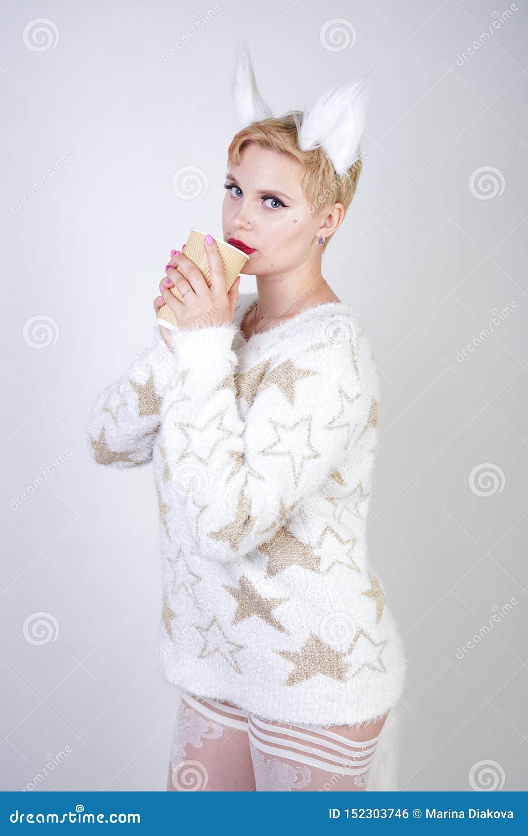 Nätt plus för kvinnawearng för formatet den caucasian stack varma tröjan mode och pälsfodra kattöron och att posera på vit studio
