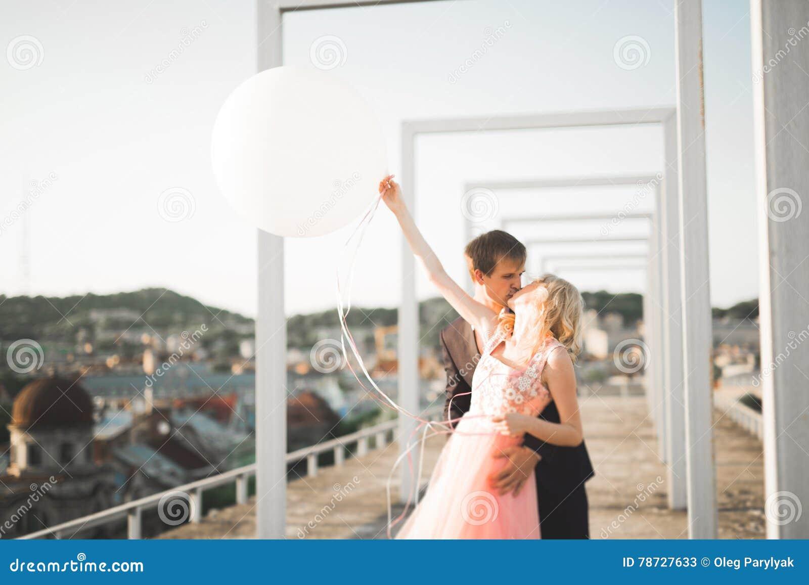 Nätt solig utomhus- stående av unga stilfulla par, medan kyssa på taket med stadssikt