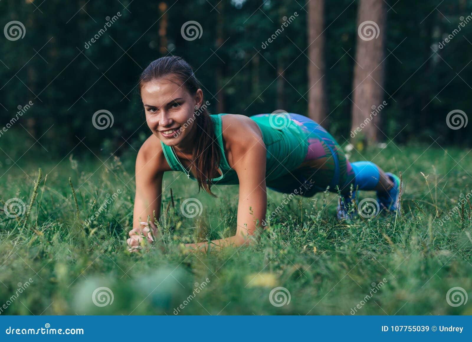 Nätt sportig ung kvinnlig idrottsman nen som gör plankövningen som ler och att se kameran som utomhus utarbetar